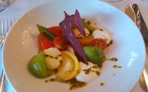 Collection of tomatoes, creamy mozzarella, crispy Serrano